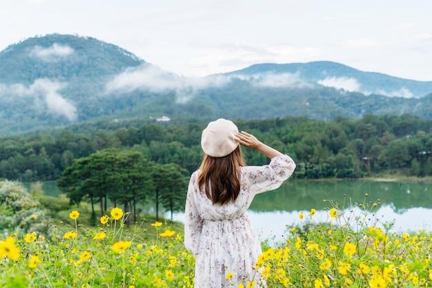Mulher asiática nova feliz que aprecia no campo de flor amarelo no por do sol.
