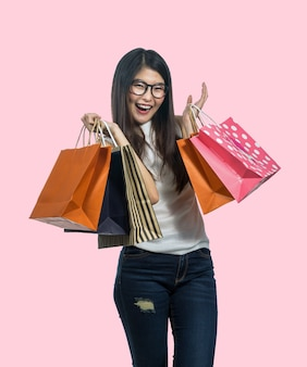 Mulher asiática nova feliz que compra no sentimento feliz e que guarda o saco de papel do produto
