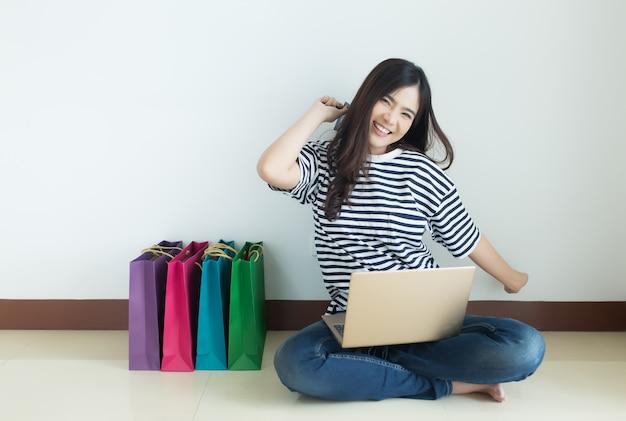 Mulher asiática nova feliz que guarda o cartão de crédito com seus portátil e sacos de compras. loja online