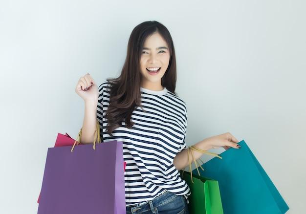 Mulher asiática nova feliz que guarda sacos de compras.