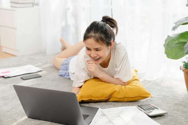 Mulher asiática nova feliz que trabalha para o laptop com originais do gráfico da casa no tapete, encontrando e treinando o conceito em linha.