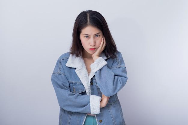 Mulher asiática nova irritada que sente a emoção negativa e má