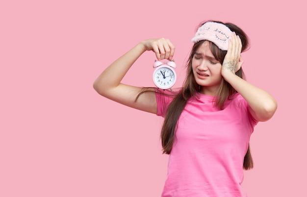 Mulher asiática nova na máscara de olho do sono que boceja e que mantém o despertador isolado no rosa. noite sem dormir