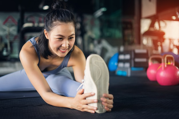 Mulher asiática nova no estilo de vida saudável do gym que senta-se na esteira da ioga que guarda o pé que estica o pé.