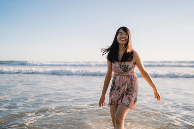 Mulher asiática nova que anda na praia. linda fêmea feliz relaxar caminhando na praia, perto do mar, ao pôr do sol na noite.