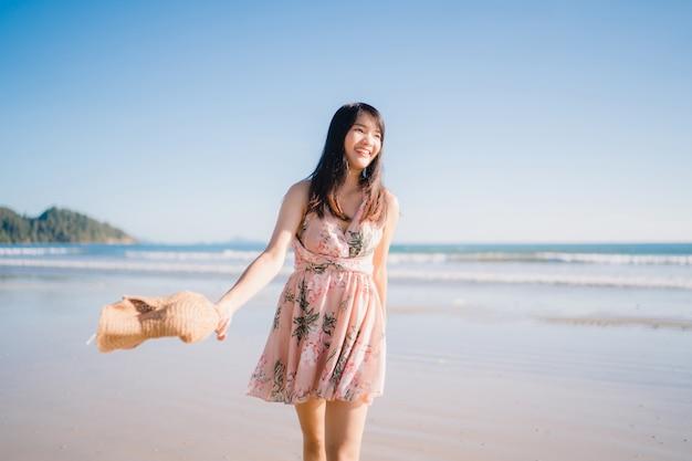 Mulher asiática nova que anda na praia. linda mulher feliz relaxar caminhando na praia