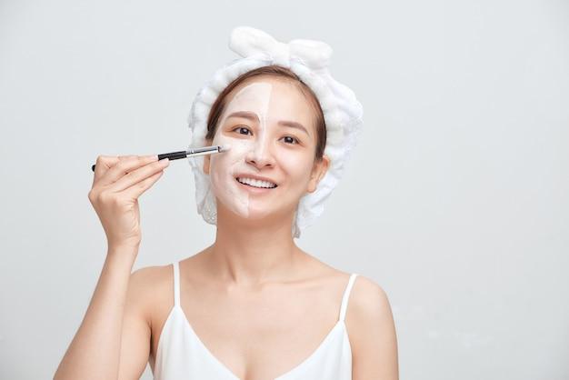 Mulher asiática nova que aplica a máscara de argila facial contra um fundo branco.