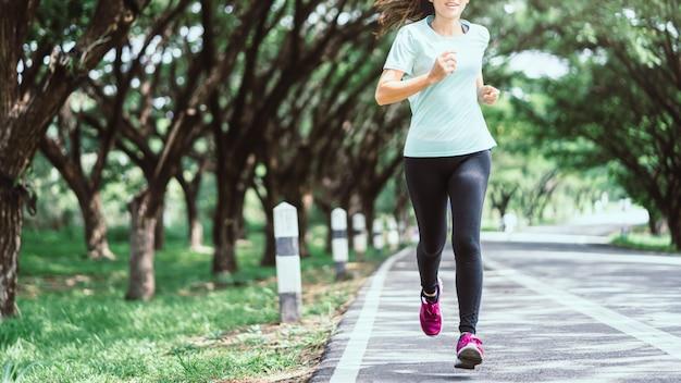 Mulher asiática nova que corre na estrada na natureza.
