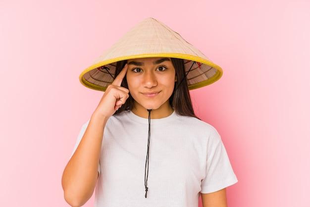 Mulher asiática nova que desgasta um chapéu vietnamita isolado mulher asiática nova que desgasta um templo de vietnamin hatpointing com o dedo, pensando, focalizado em uma tarefa.
