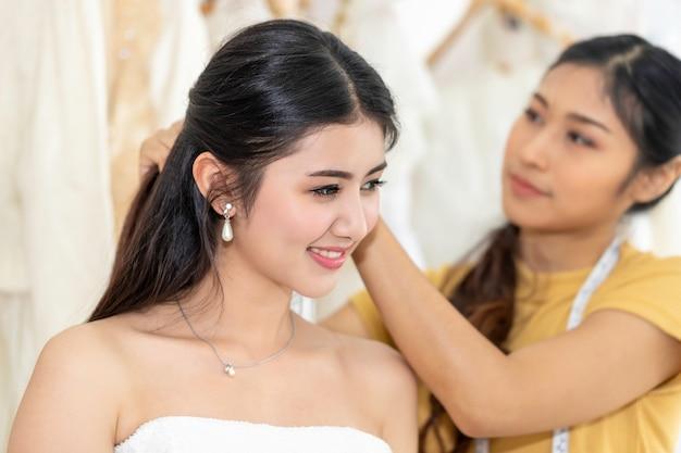 Mulher asiática nova que escolhe o vestido de casamento em uma loja com assistente do alfaiate.