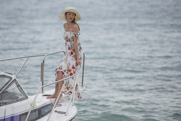 Mulher asiática nova que está na parte dianteira da plataforma de barco que olha em uma opinião larga do mar com cabelo longo do vento.