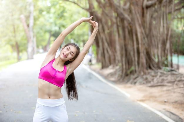 Mulher asiática nova que estica o corpo após o exercício no parque