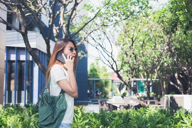 Mulher asiática nova que fala no smartphone no jardim no fim de semana. mulher jovem, usando, smartphone, f