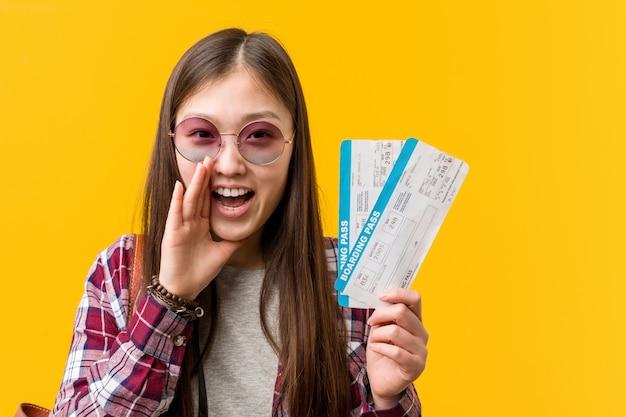 Mulher asiática nova que guarda gritos dos bilhetes aéreos entusiasmado à parte dianteira.