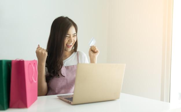 Mulher asiática nova que guarda o cartão de crédito e que usa o laptop.