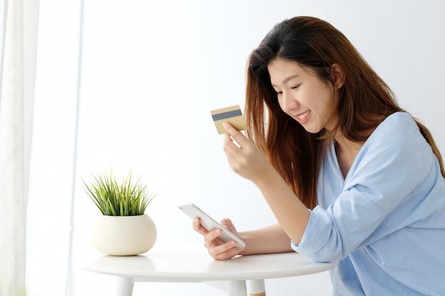 Mulher asiática nova que guarda o cartão de crédito e que usa o telefone esperto para comprar em linha