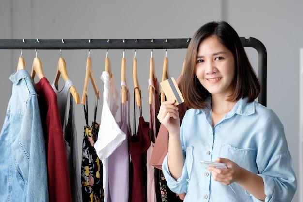 Mulher asiática nova que guarda o cartão de crédito e que usa o telefone esperto para o conceito em linha do negócio, do negócio e da tecnologia, pagamento em linha, dinheiro digital
