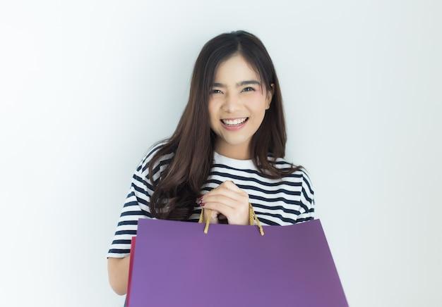Mulher asiática nova que guarda sacos de compras. compras on-line e conceito de navegação.