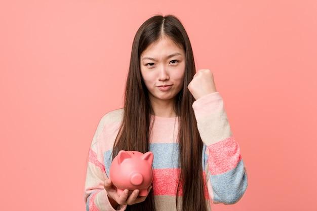 Mulher asiática nova que guarda um mealheiro que mostra o punho à câmera, expressão facial agressiva.