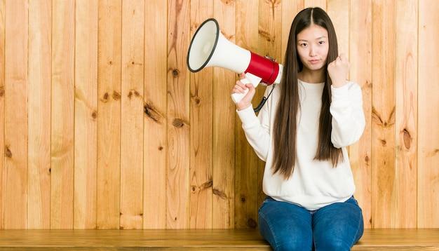 Mulher asiática nova que guarda um megafone que mostra na expressão facial agressiva.