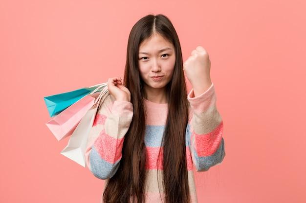 Mulher asiática nova que guarda um saco de compras que mostra o punho à câmera, expressão facial agressiva.