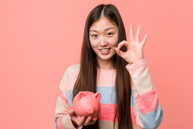 Mulher asiática nova que mantém um mealheiro alegre e seguro mostrando o gesto aprovado.