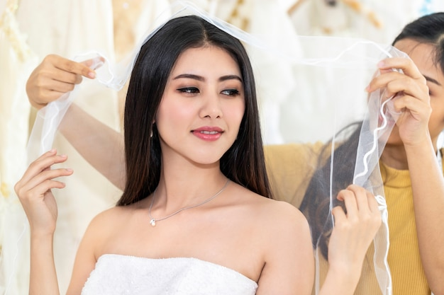 Mulher asiática nova que mede no vestido de casamento em uma loja pelo alfaiate.