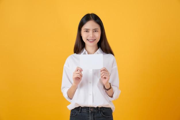 Mulher asiática nova que prende o papel em branco com cara de sorriso e que olha na parede amarela. para sinais de publicidade.