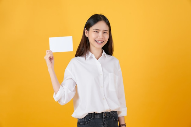 Mulher asiática nova que prende o papel em branco com cara de sorriso e que olha no fundo amarelo. para sinais de publicidade.