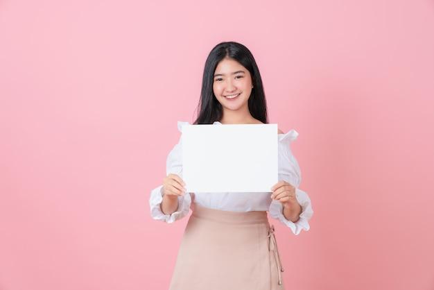 Mulher asiática nova que prende o papel em branco com cara de sorriso e que olha no fundo cor-de-rosa. para sinais de publicidade.
