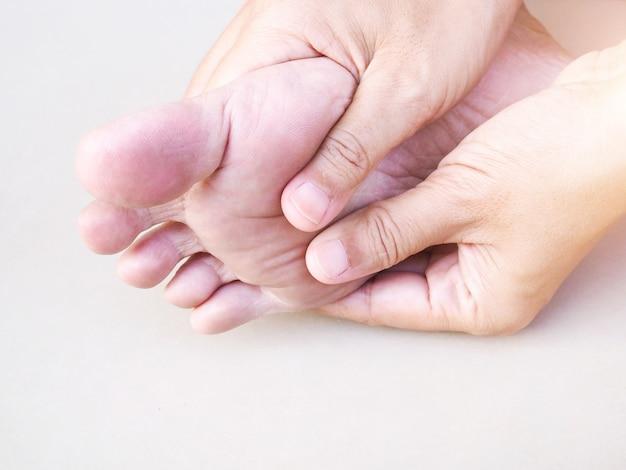 Mulher asiática nova que sofre de dor no tornozelo, dor no calcanhar e solas dos pés usando a mão para massagear o corpo para aliviar a dor, sintoma médico e conceito dos cuidados médicos.