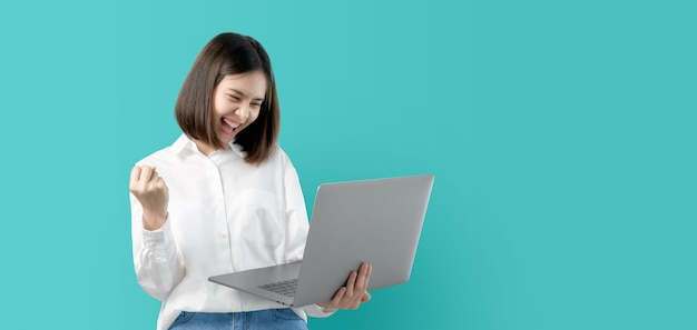 Mulher asiática nova que sorri guardando o laptop com mão do punho e entusiasmado para o sucesso.