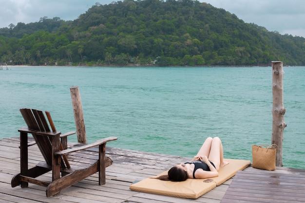 Mulher asiática nova que sunbathing na praia, estilo de vida asiático da mulher.