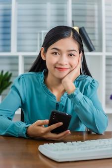 Mulher asiática nova que trabalha em casa após a pandemia do coronavírus (covid-19) no mundo.