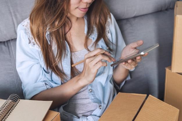 Mulher asiática nova que trabalha o negócio em linha usando o telefone esperto