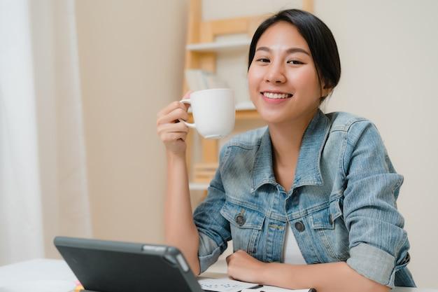 Mulher asiática nova que trabalha usando a tabuleta que verifica meios sociais e que bebe o café quando relaxe na mesa na sala de visitas em casa.
