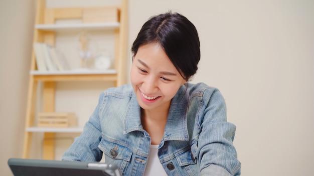 Mulher asiática nova que trabalha usando a tabuleta que verifica meios sociais quando relaxa na mesa na sala de visitas em casa.