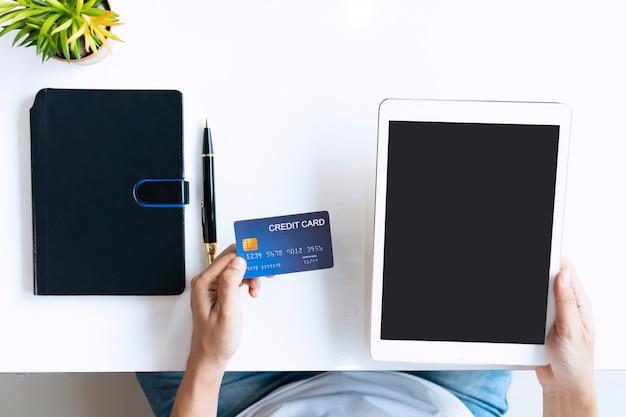 Mulher asiática nova que usa a tabuleta ao guardar o cartão de crédito na mesa na sala de visitas em casa, na vista superior e no espaço da cópia.