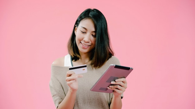 Mulher asiática nova que usa a tabuleta que compra a compra em linha pelo cartão de crédito que sente o sorriso feliz na roupa ocasional sobre o tiro cor-de-rosa do estúdio do fundo. a mulher contente adorável de sorriso feliz exulta o sucesso.