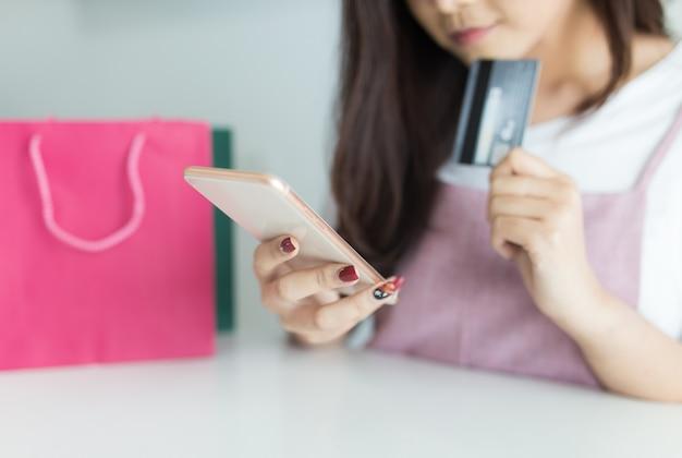 Mulher asiática nova que usa o smartphone e guardando o cartão de crédito.