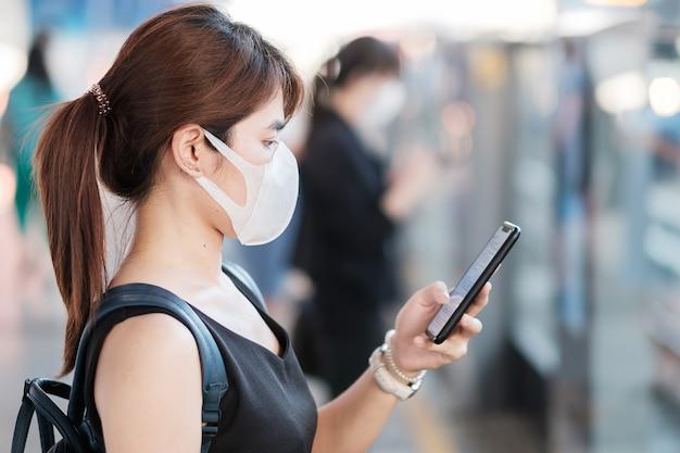 Mulher asiática nova que veste a máscara protectora cirúrgica contra o coronavírus novo ou a doença de vírus da corona (covid-19) na estação de caminhos-de-ferro pública.