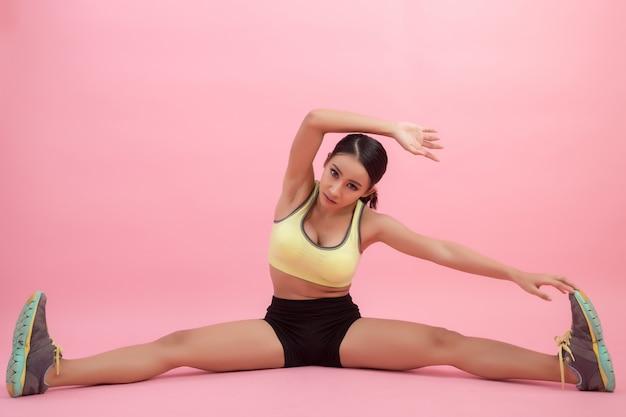 Mulher asiática nova saudável bonita que faz um exercício de esticão antes de jogar um esporte.