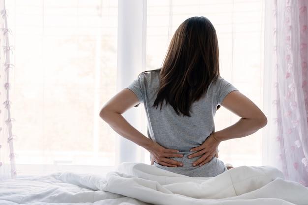 Mulher asiática nova triste que toca para trás que sente a dor nas costas dor da manhã dor renal muscular lombar baixa senta-se na cama depois que o sono ruim acorda na dobra desconfortável do colchão. conceito de estiramento de mulher