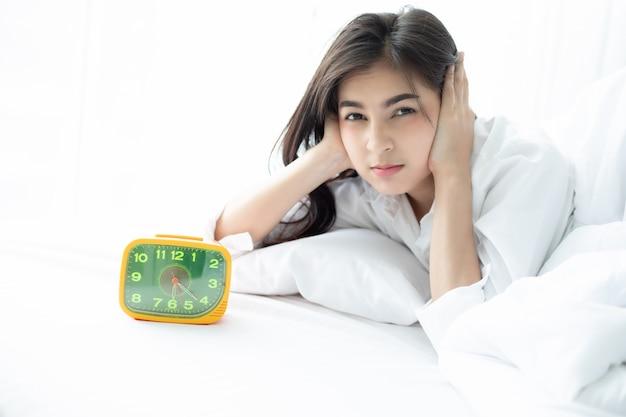 Mulher asiática odeia acordar cedo de manhã. menina sonolenta, olhando para o despertador