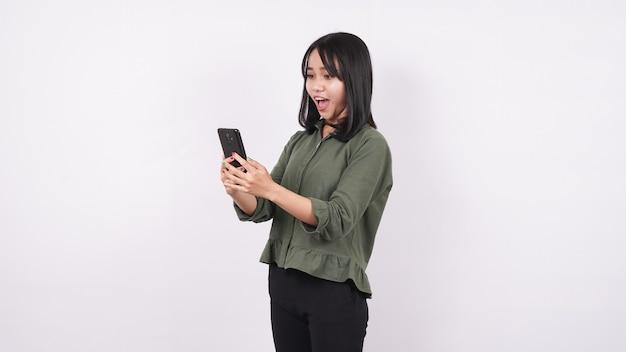 Mulher asiática olha para o celular com uma expressão de choque isolada em uma parede branca Foto Premium