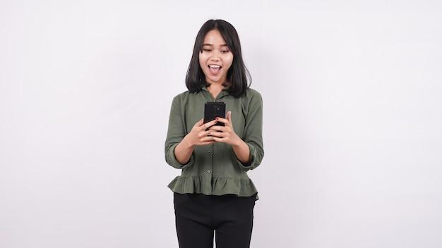 Mulher asiática olha para o celular com uma expressão de choque isolada em uma parede branca