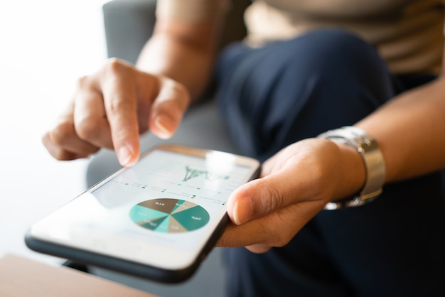 Mulher asiática olhando alguns gráficos em seu telefone celular enquanto está sentado na cafeteria
