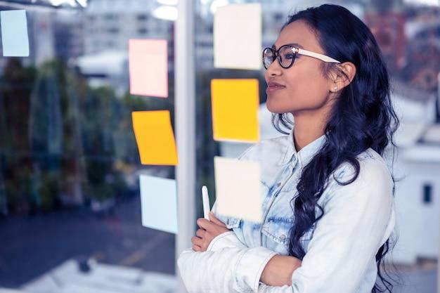 Mulher asiática olhando notas auto-adesivas na parede de vidro