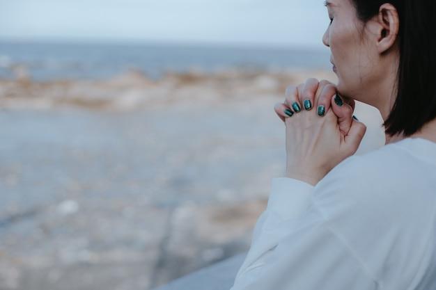 Mulher asiática orando a deus na praia