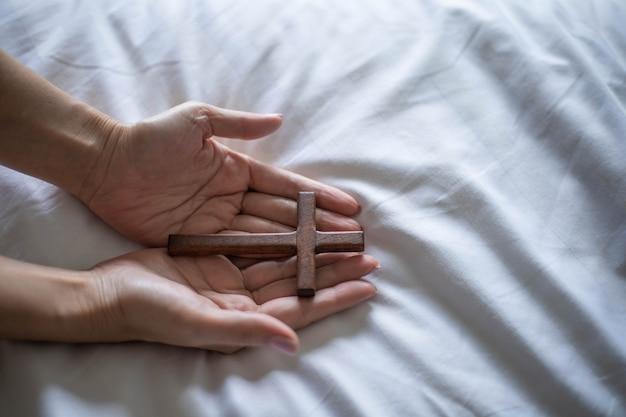 Mulher asiática orando com uma cruz de madeira pela manhã.